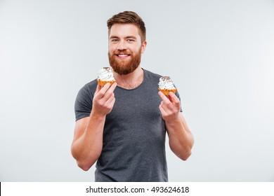 Happy bearded man holding two cream cakes isolated on white background