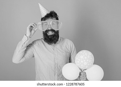 Happy bearded man in huge glasses posing with bright balloons, fun concept. Comedian with crazy look entertaining guests at special event. Perfomer with wild beard guiding contest at birthday party.