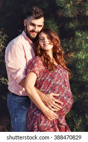 Happy bearded man hugging brunette pregnant woman from behind