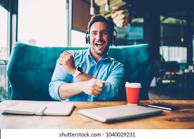 Happy bearded man in modern headphones dancing for favourite song sitting at table.Positive male entrepreneur listening music from playlist and singing enjoying free time in stylish coffee shop