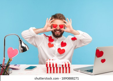 Happy bearded man office worker in white shirt all covered with sticky hearts holding toy red hearts near eyes and smiling, showing his love. Indoor studio shot isolated on blue background