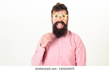 Happy bearded man on white background, birthday fun concept. Man with long beard and open mouth wearing star shaped glasses. Hipster with excited look and trendy beard posing with party accessories.