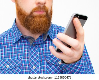 Happy bearded man pointing on smartphone on white background. man in blue shirt. Smiling man with beard with mobile phone in hands, studio shot.