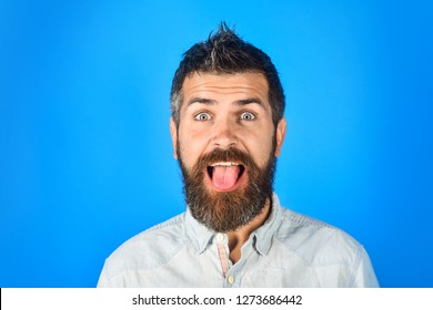 Happy bearded man shows tongue. Handsome businessman sticking tongue out happy with funny expression. Positive young man. Emotion concept. Fashionable man with short hair in casual wear.