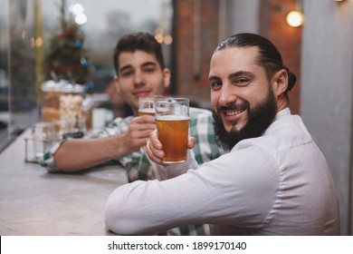 Happy bearded man smiling to the camera, holding up his beer glass at the pub