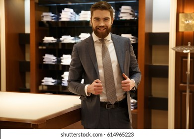 Happy bearded man in suit posing in shop while holding his jacket and looking at camera