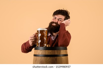 Happy bearded man with wooden barrel of beer and mug of beer. Oktoberfest. Craft beer at restaurant. Holliday, drinks, alcohol, leisure concept. Bearded man with glass and barrel with craft beer.