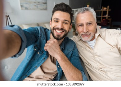 happy bearded son taking selfie with retired cheerful father at home