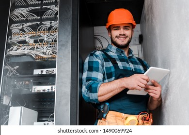 happy bearded technician in safety helmet holding digital tablet
