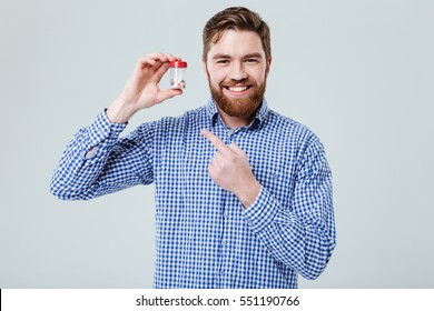 Happy bearded young man holding and pointing on bottle of pills