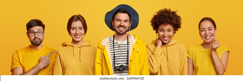 Happy bearded young man with retro camera and headgear, positive women in sweatshirts, Asian lady makes korean like sign, surprised guy indicates away. People in yellow clothes. Monochrome shot.