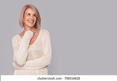 happy beautidul middle aged woman isolated on grey background