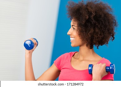 Happy beautiful African American woman exercising in the gym lifting weights as she uses a pair of dumbbells to strengthen her arm muscles