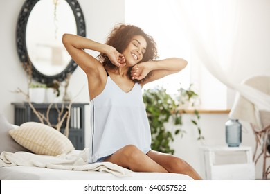 Happy beautiful african girl in sleepwear stretching smiling with closed eyes sitting on bed at home woke up in the morning on a sunny day.