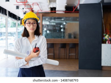 Happy beautiful asian female construction worker wearing yellow hard hat and hand holding blueprints at construction sites office.