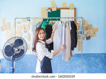 Happy beautiful asian housewife is arranging the clothes on Clothesline, living home concept.