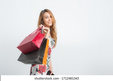 Happy beautiful asian woman carrying shopping bags on isolated gray background, summer sale concept.