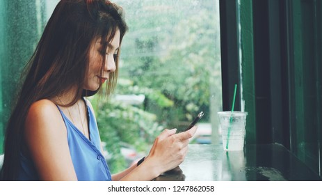 Happy beautiful asian woman chatting with boyfriend by smartphone in cafe
