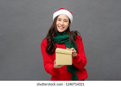 Happy beautiful Asian woman in colorful Christmas attire opening gift box studio shot isolated on gray background