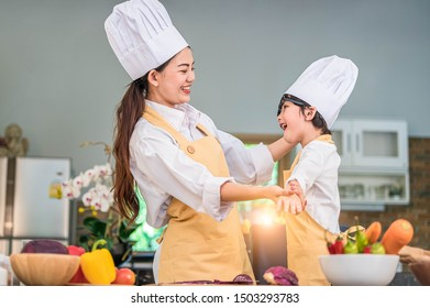 Happy beautiful Asian woman dress up cute little boy chef outfit for prepare to cooking in home kitchen. People lifestyles and Family. Homemade food and ingredients concept. Two Thai people life