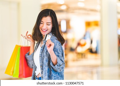 Happy beautiful Asian woman smile at credit card, hold shopping bags, copy space on shopping mall background. Shopaholic people, retail special offer price, holiday vacation activity lifestyle concept