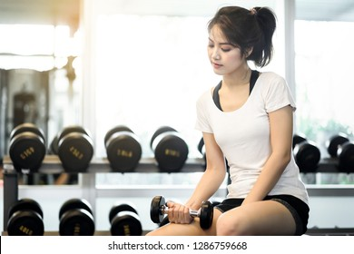 Happy beautiful asian woman smiling and lifting dumbbells cheerful in sports fitness gym , excersie and healthcare concept