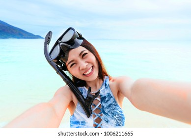 Happy beautiful Asian woman with snorkeling mask taking selfie on the beach near the sea
