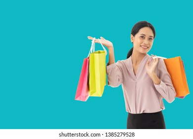 happy beautiful asian women smile two hand holding shopping bags, copy space isolate over blue background