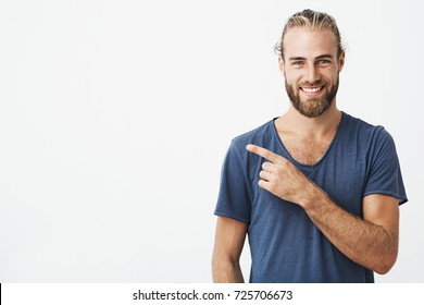 Happy beautiful bearded guy with good-looking hairstyle looking at camera, smiling and pointing aside with hand. Copy space.