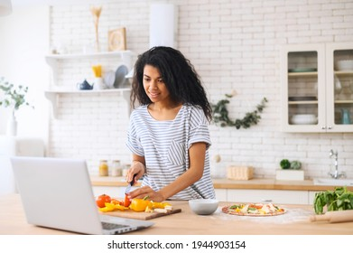 Happy beautiful biracial woman enjoying cooking and filming it, looking for a recipe on the laptop in the modern kitchen, food blogger concept, healthy lifestyle, online learning cooking class concept