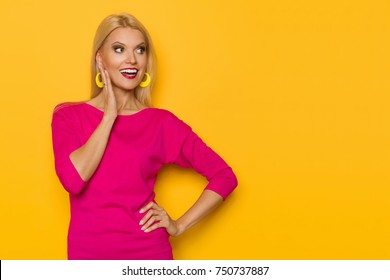 Happy beautiful blond woman in pink sweater is standing with hand on chin, looking away and talking. Waist up studio shot on yellow background.