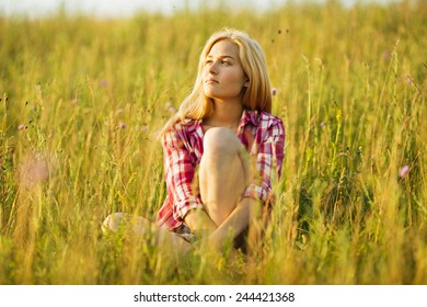 Happy beautiful blonde girl sitting on grass