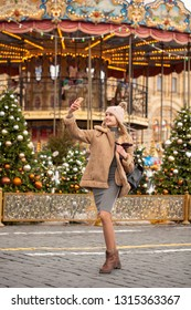 Happy Beautiful blonde woman in a sheepskin coat and knitted hat taking pictures of himself on a cell phone in the center of the Christmas courtyard