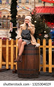 Happy Beautiful blonde woman in a sheepskin coat and knitted hat sitting on a wooden barrel in the center of the Christmas courtyard