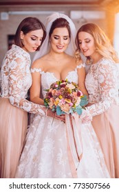 Happy beautiful bride with bridesmaids on wedding day, indoors. Girls with wedding flowers bouquet.