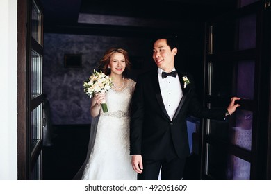 happy and beautiful bride and groom standing together in a dark room