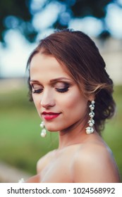 happy beautiful bride with hairstyle and artistic smoky eyeshadow and smiling on bokeh background.