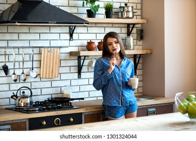 Happy beautiful brunette woman is in the kitchen with a cup of tea or coffee in blue pajamas. Early morning rise is a good habit