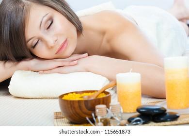 happy beautiful brunette woman relaxing  in spa salon