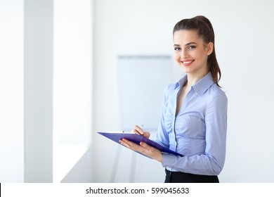 Happy beautiful business woman with clipboard in the office. Copy space