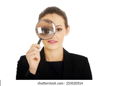 Happy beautiful businesswoman with magnifying glass.