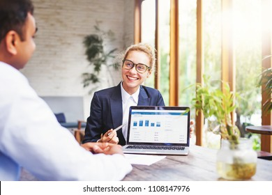 Happy beautiful businesswoman presenting charts to the client on a screen of laptop