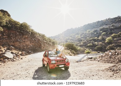 Happy beautiful carefree young woman having fun sitting on bonnet of convertible 4x4 car in mountains - road trip adventure concept