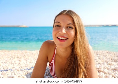 Happy beautiful cheerful smiling woman enjoying relax lying on the beach looking at camera. Summer holidays concept.