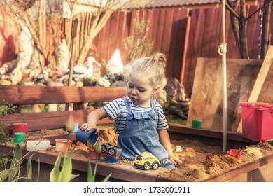 Joyeuse et belle petite fille jouant seule dehors sur une aire de jeux avec des voitures de jouets dans un bac à sable à la campagne symbolisant le mode de vie de l'enfance