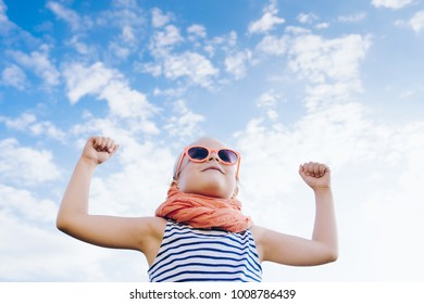 Happy beautiful child girl in sunglasses with open hands against the sky background. Girl Power Concept