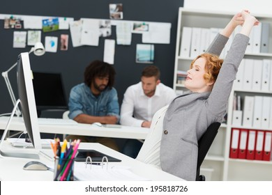 Happy beautiful contented young businesswoman relaxing in her chair stretching her arms in the air in a busy office with multiethnic male business partners