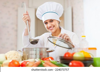 Happy beautiful cook works with ladle at commercial kitchen