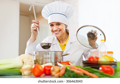 Happy beautiful cook works with ladle