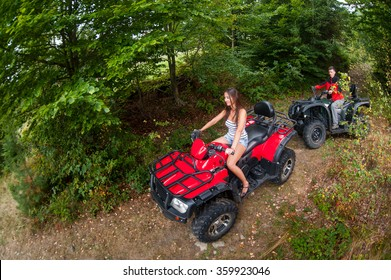 Happy beautiful couple driving four-wheelers ATV. Girl is leading the way